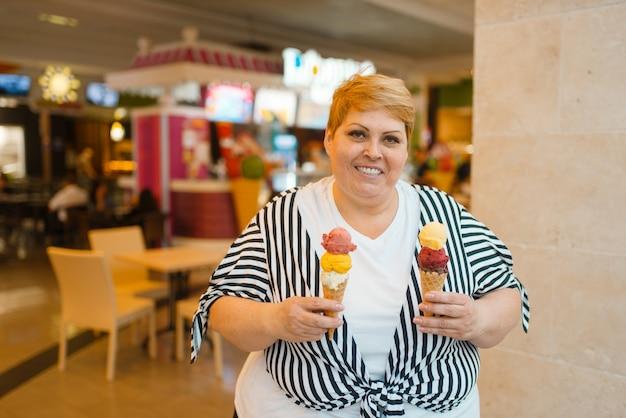 Gruba kobieta trzyma lody w restauracji fastfood mall, niezdrowa żywność. kobieta z nadwagą z lodami, problem z otyłością