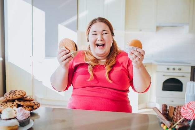 Gruba młoda kobieta w kuchni siedzi i jedzenie fast foodów.
