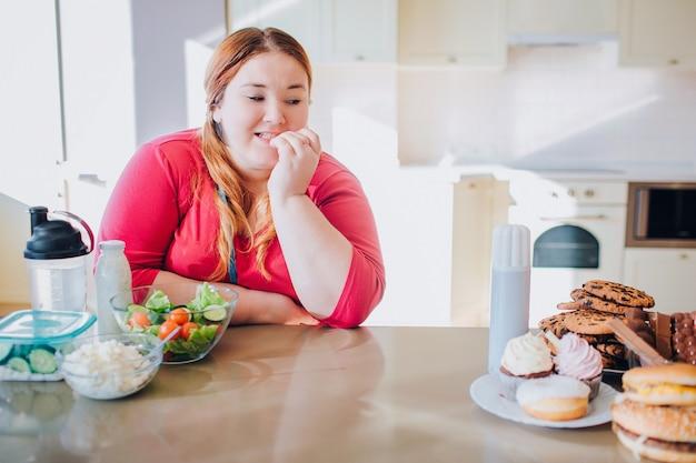 Gruba młoda kobieta w kuchni siedzi i jedzenie. patrząc na słodki śmieciowy posiłek po lewej stronie. pokusa. zdrowe jedzenie po lewej stronie.