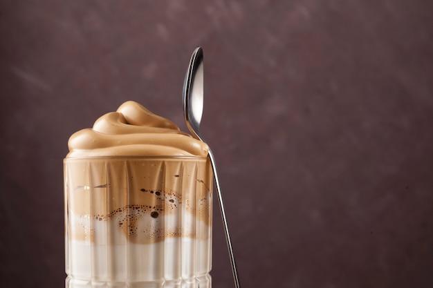 Gruba, pięknie ułożona bita pianka na szklance kawy dalgona. tradycyjny koreański napój.