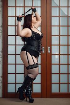 Gruba przewrotna kobieta w erotycznej bieliźnie trzymając skórzany bicz.