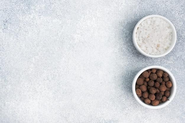 Gruba sól i czarne ziarna pieprzu w białych ceramicznych miseczkach na szarym betonie, widok z góry miejsca na kopię.