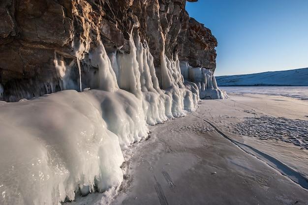 Gruba warstwa lodu na skale oświetlonej słońcem