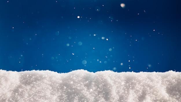 Gruba warstwa śniegu na niebieskim tle. zimowe wakacje tło z teksturą śniegu.