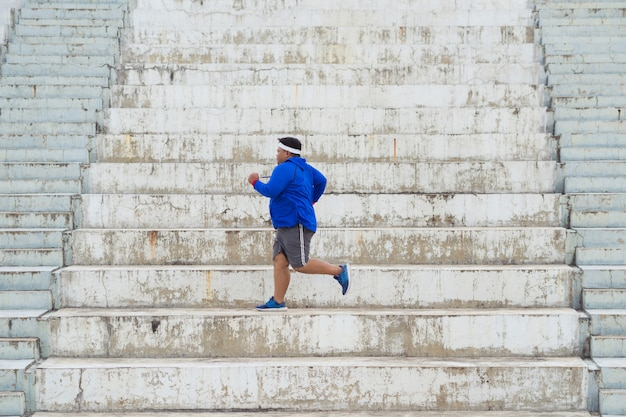 Grubas biega po schodach