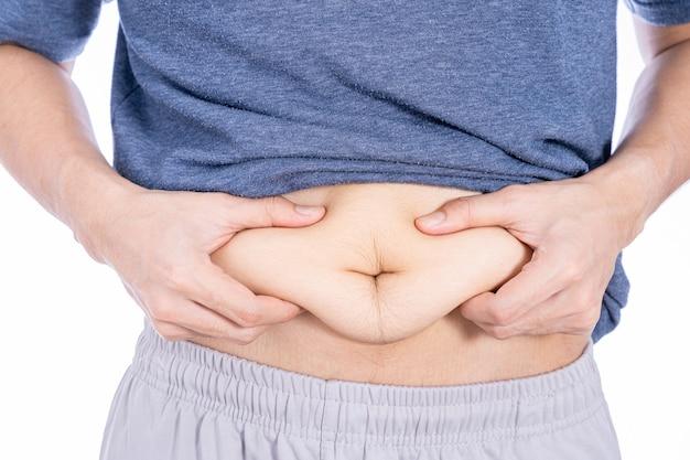 Grubas posiadający nadmierny brzuch tłuszczu na białym tle białej ściany.