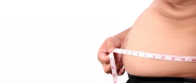 Grubas ręka trzyma nadmiar tłuszczu z brzucha z miarką na białym tle