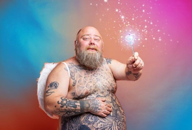 Grubas szczęśliwy z tatuażami na brodzie i skrzydłami zachowuje się jak magiczna wróżka