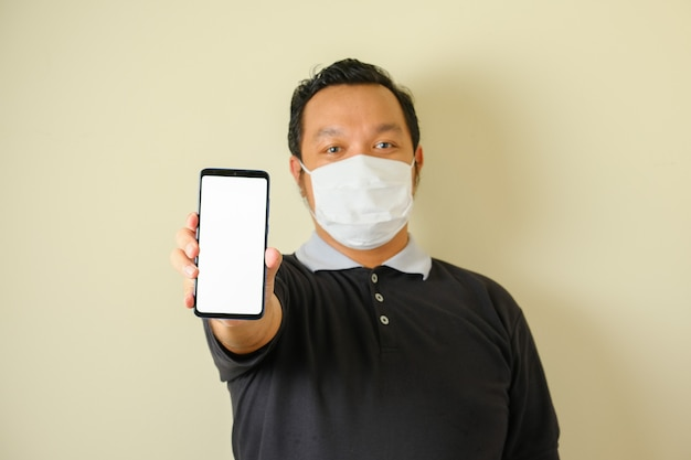 Grubas w masce z poważną miną wskazuje na swój smartfon. gest wskazał. niebieskie tło