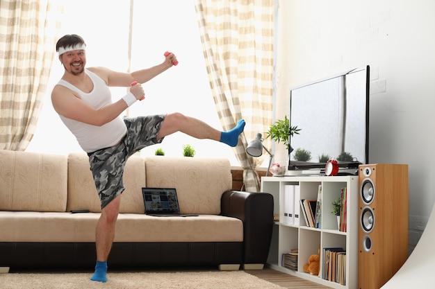 Grubas w odzieży sportowej i hantlach wykonuje ćwiczenia fizyczne