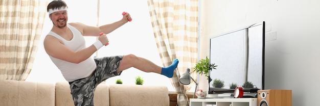 Grubas w stroju sportowym i z hantlami wykonuje ćwiczenia fizyczne