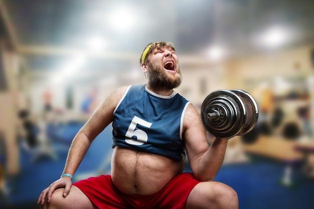 Grubas wykonuje ciężkie ćwiczenia z hantlami na siłowni