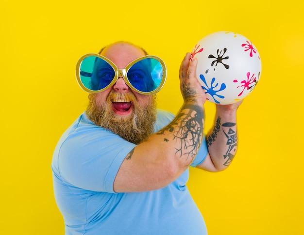 Grubas z brodą i okularami przeciwsłonecznymi bawi się piłką