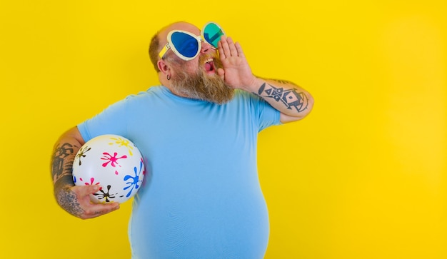 Grubas z brodą i okularami przeciwsłonecznymi krzyczy z piłką w ręku