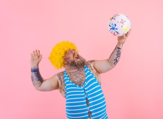Grubas z brodą i peruką bawi się piłką