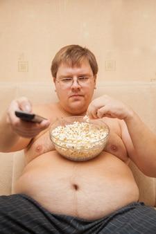 Grubas z brzuchem piwa przed telewizorem jedzenie popcornu