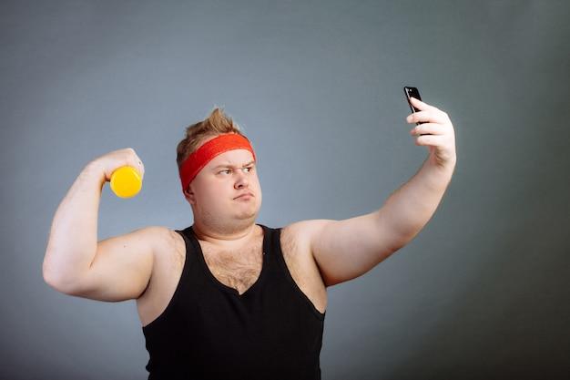 Grubas z dużym brzuchem, trzymając hantle, robi selfie na szarej ścianie