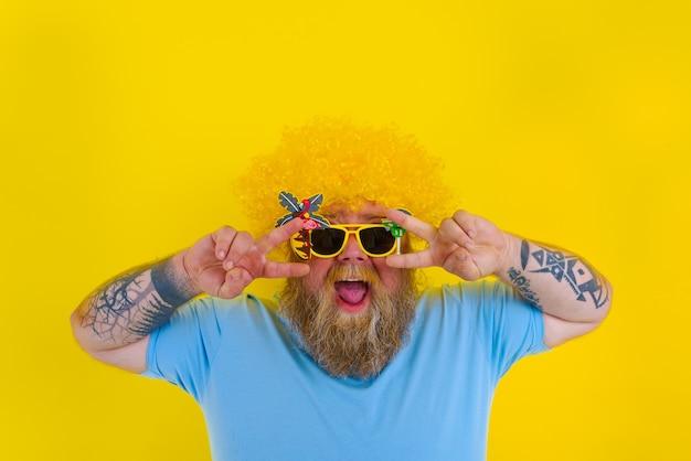 Grubas z peruką na głowie i okularami przeciwsłonecznymi tańczy