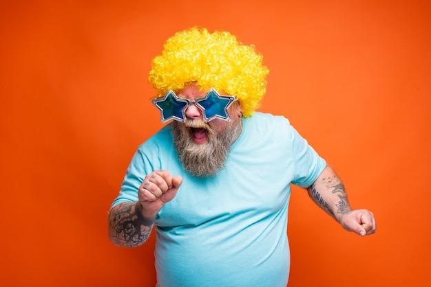 Grubas z tatuażami na brodzie i okularami przeciwsłonecznymi śpiewa piosenkę