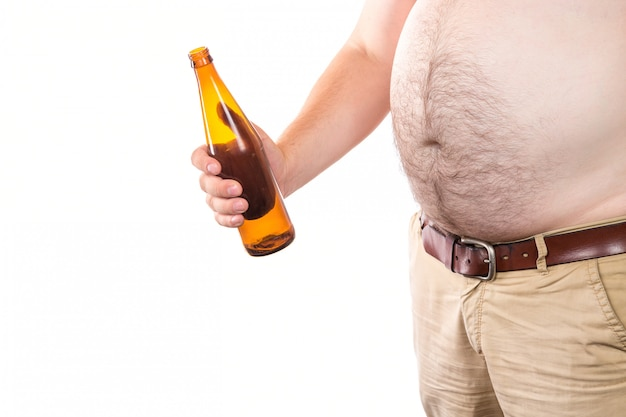 Grubas z wielkim brzuchem trzymając butelkę piwa na białym tle