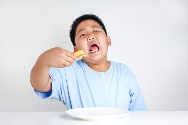 Grube dzieciaki radośnie jedzą pizzę. spożywana w dużych ilościach tkanka tłuszczowa nie jest zdrowa.