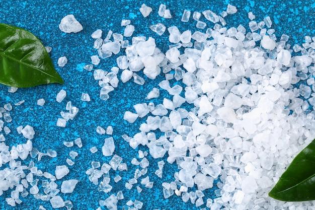 Grube kryształy soli na niebieskim stole