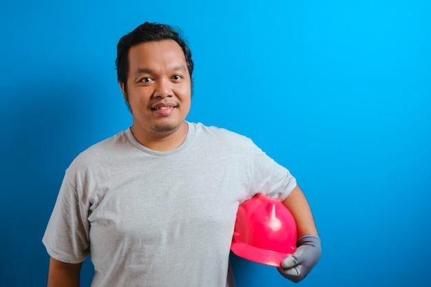 Gruby azjata trzymający czerwony kask z ręką uśmiecha się do kamery pewnym siebie gestem