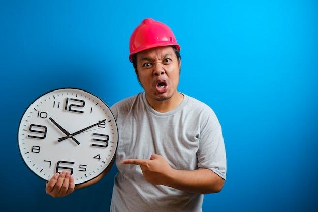 Gruby azjata używa gniewnego wyrazu twarzy, wskazując palcem na zegar, ponieważ pracownik spóźnia się na miejsce pracy. przepracowana koncepcja