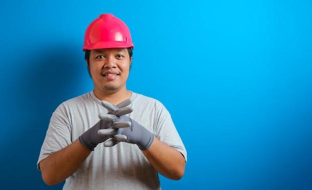 Gruby azjata w czerwonym kasku uśmiecha się do kamery, krzyżując ramiona pewnym siebie gestem