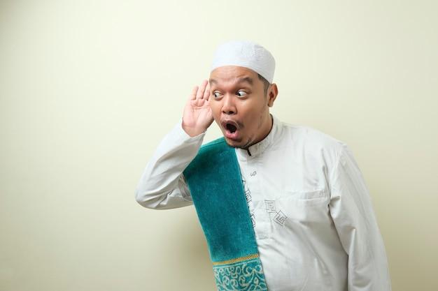 Gruby azjatycki muzułmanin słucha szeptów z śmieszną miną zaciekawiony wsłuchuje się w soczyste plotki