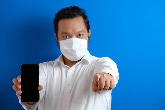 Gruby azjatycki pracownik biurowy w masce wskazuje na swój smartfon z poważnym spojrzeniem. gest wskazał. niebieskie tło