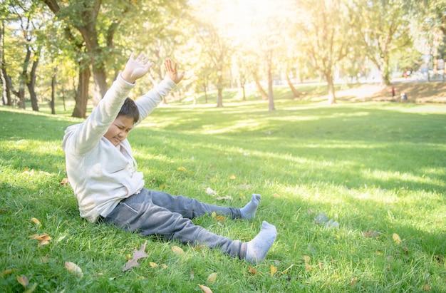 Gruby chłopak rozciąga się w parku