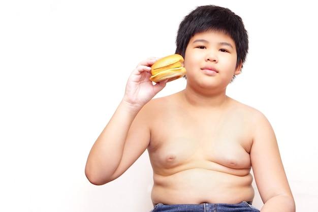 Gruby chłopiec trzymający hamburgera na białym tle.