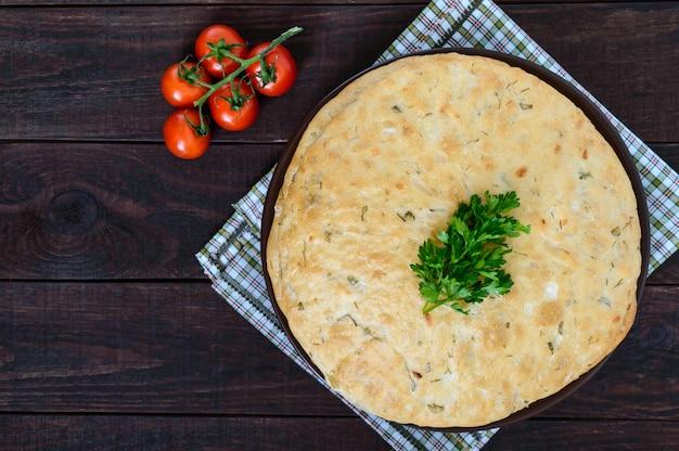 Gruby flapjack - chleb pita z zielenią na ciemnym drewnianym tle. tradycyjne danie azjatyckie. widok z góry