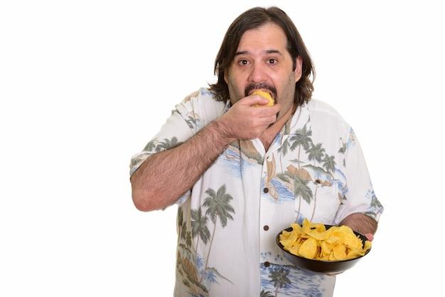 Gruby mężczyzna rasy kaukaskiej jedzenie kęs żetonów gotowy na wakacje na białym tle