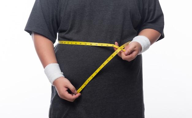Gruby mężczyzna trzyma pomiar taśmy dla kasy out jego ciało odizolowywający na białym tle