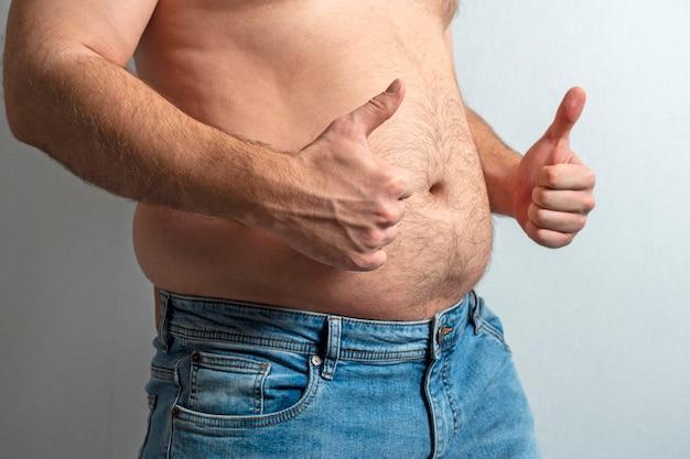 Gruby mężczyzna w dżinsach z nagim brzuchem i palcem uniesionym w górę. pojęcie pozytywności ciała. samoakceptacja