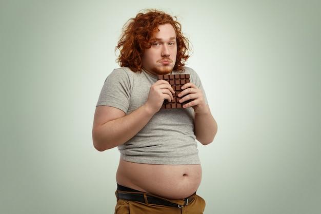 Gruby mężczyzna z nadwagą i rudymi kręconymi włosami wyglądający na niezdecydowanego i niezdecydowanego, trzymający oburącz dużą tabliczkę czekolady, podczas gdy nie wolno mu jeść cukru, i fast foody z powodu ścisłej diety niskowęglowodanowej