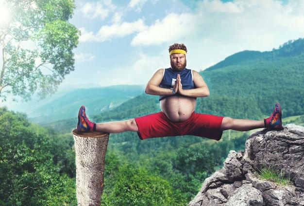 Gruby sportowiec robi szpagat w górach
