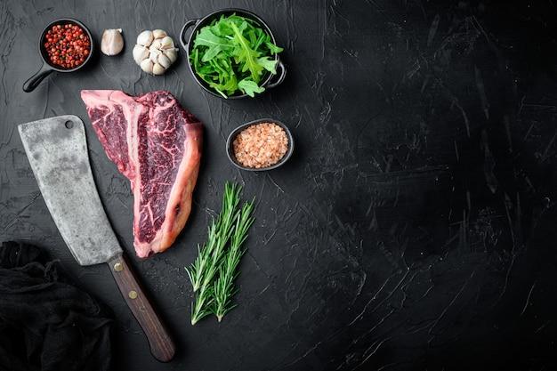 Gruby surowy stek t-bone z zestawem przypraw i rozmarynu, na czarnym kamiennym stole, płaski widok z góry