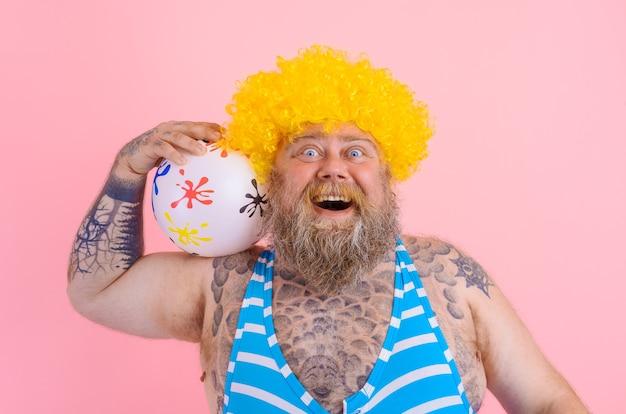 Gruby szczęśliwy mężczyzna z brodą i peruką bawi się piłką