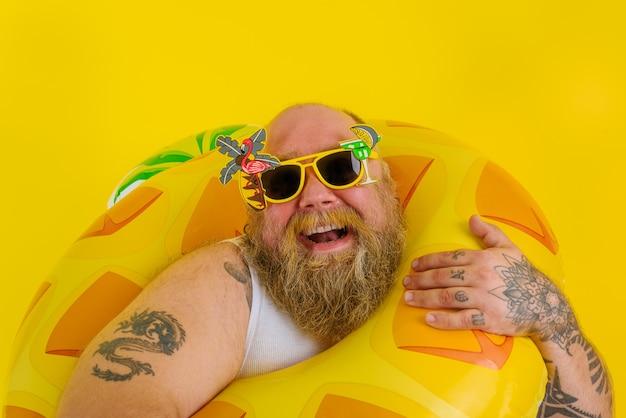 Gruby szczęśliwy mężczyzna z peruką w głowie jest gotowy do pływania z ratownikiem w kształcie pączka