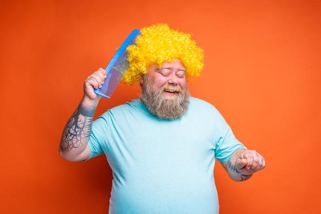 Gruby szczęśliwy mężczyzna z tatuażami na brodzie i okularami przeciwsłonecznymi czesze się gigantycznym grzebieniem