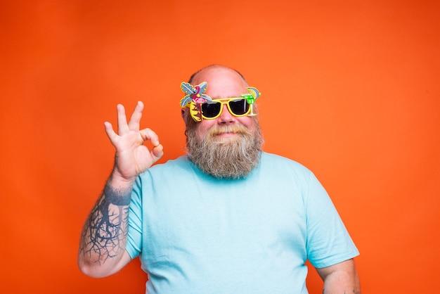 Gruby szczęśliwy mężczyzna z tatuażami na brodzie i okularami przeciwsłonecznymi jest gotowy na lato