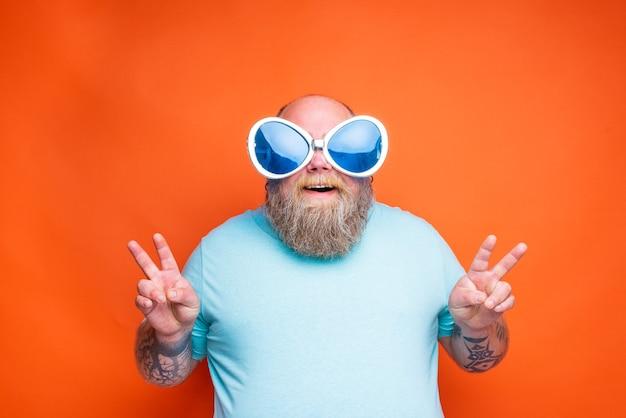 Gruby szczęśliwy mężczyzna z tatuażami na brodzie i okularami przeciwsłonecznymi robi znak zwycięstwa rękami