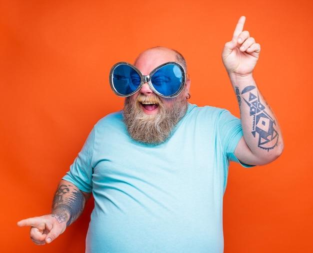 Gruby szczęśliwy mężczyzna z tatuażami na brodzie i okularami przeciwsłonecznymi tańczy muzykę