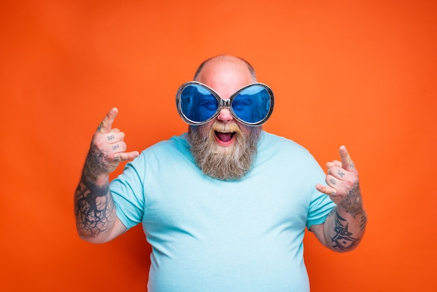 Gruby szczęśliwy mężczyzna z tatuażami na brodzie i okularami przeciwsłonecznymi wykonuje gest rogów