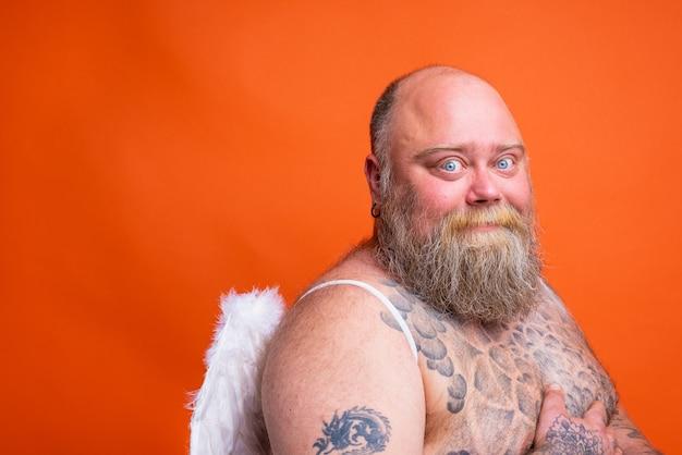 Gruby szczęśliwy mężczyzna z tatuażami na brodzie i skrzydłami zachowuje się jak anioł