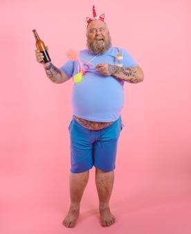 Gruby szczęśliwy mężczyzna zachowuje się jak szczęśliwe dziecko, ale pije piwo