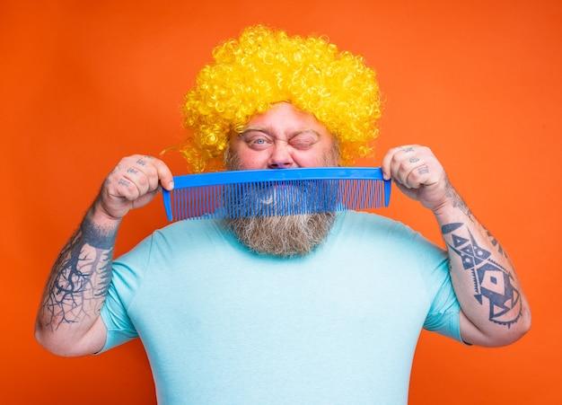 Gruby wątpiący mężczyzna z tatuażami na brodzie i okularami przeciwsłonecznymi czesze się gigantycznym grzebieniem